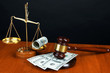 Gavel,scales and money on table on black background
