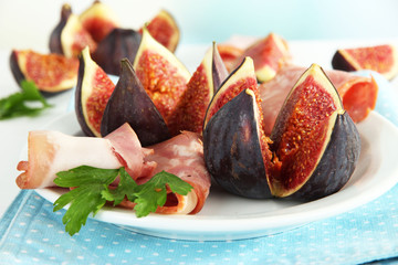 Tasty figs with ham on plate