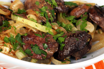 Fried chicken livers in pan close-up