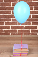 Color balloon with books on brick wall background