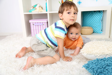 Cute little boys on floor in room