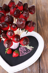 Strawberry in chocolate on skewers in cup on table close-up