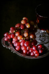 Vintage style image of red grapes and a glass of wine