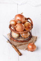 Brown onions on a white wooden background