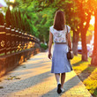 Girl walking away through green alley at the sunset