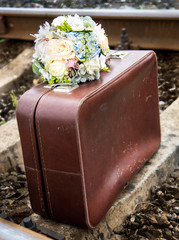 Old suitcase with a beautiful wedding bouquet on the rails
