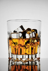 Faceted amber glass with whiskey and ice