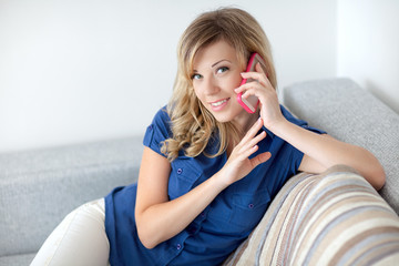 beautiful girl sitting on a sofa and talking on the phone