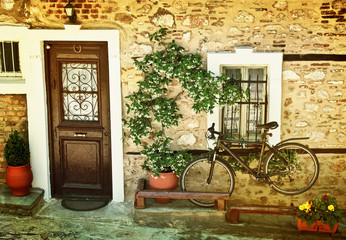 Black  bicycle against old house wall.