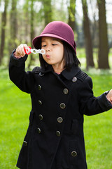 Asian girl blowing soap bubbles