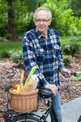 Male cyclist with wicker basket full of groceries