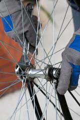 Hands repairing bicycle wheel using wrench