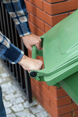 Male hands pushing a wheeled dumpster