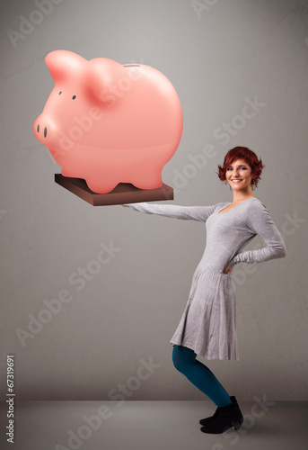canvas print picture Young girl holding a huge savings piggy bank