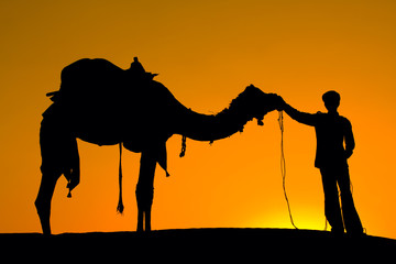 Silhouette of a man and camel at sunset in India