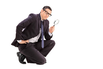 Male inspector looking through a magnifying glass
