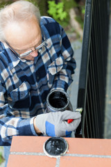 Gray-haired man painting modern metal gate
