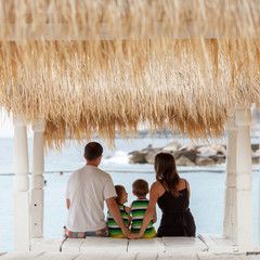 Back view of a happy family, sitting on the beach, watching the