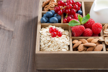 box with breakfast items - oatmeal, granola, nuts, berries and