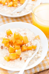 oatmeal with fresh apricots and nuts, orange juice, top view