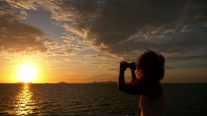 Woman Taking a Photo of Sunset from the Sailing Boat. Slow