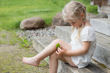 Child with injury on knee holding plantain leaf to heal it
