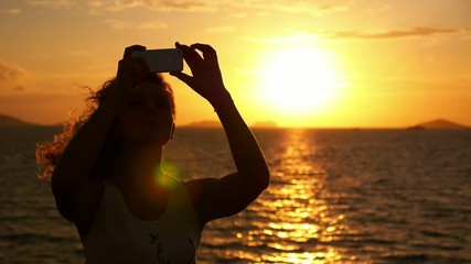 Woman Taking Pictures with Smartphone at Sunset. Selfie against