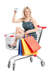 Young woman riding in a shopping cart