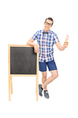 Young man standing by a blackboard