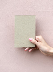 Greeting card in woman hand on wall background
