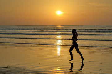 Silhouette of woman jogger running on sunset beach