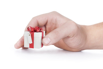 female hand holding red and white gift box with a bow