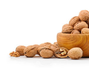 Wooden bowl full of walnuts on white background