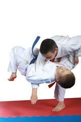 Boy with orange belt is doing throw judo