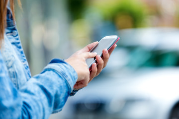 Mobile phone in a woman's hand. Outdoor image.