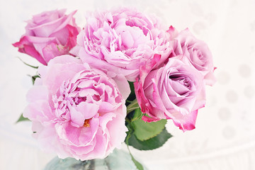 Close-up floral composition with a pink peony and roses
