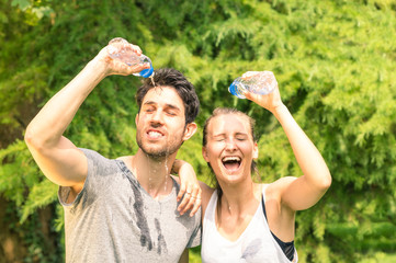 Sporty couple refreshing with water after run training in park