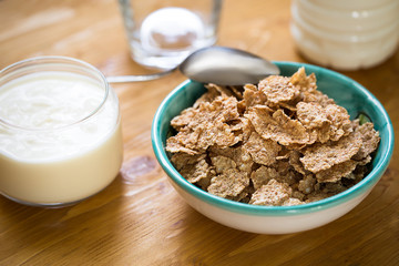 Delicious and healthy wheat flakes in bowl with yogurt