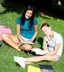 Smiling happy female students in college with books