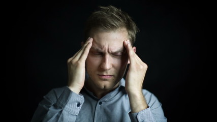 Portrait of stressed man with headache on black background