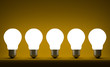 Row of glowing tungsten light bulbs on yellow