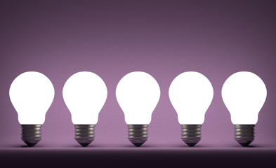Row of glowing tungsten light bulbs on violet