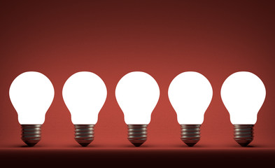 Row of glowing tungsten light bulbs on red