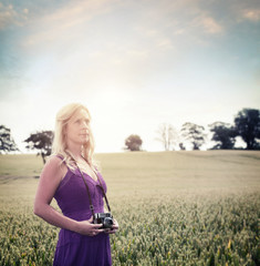 woman in field holding retro camera