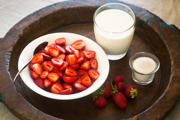 Strawberries in a bowl with milk and sugar