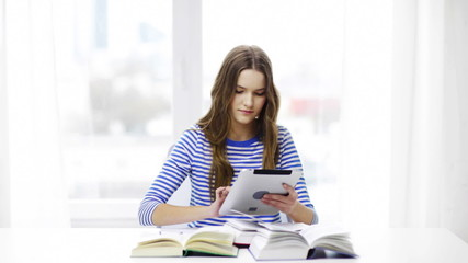smiling student girl with tablet pc and books