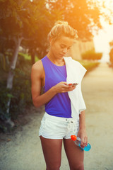Blond sporty girl looking to the telephone screen taking break