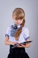 Little schoolgirl smiling while using digital tablet at desk