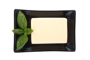 Block of butter and mint leaf on plate