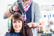 canvas print picture - Friseur föhnt Frau die Haare im Friseursalon